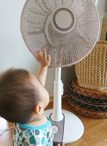 赤ちゃんが扇風機に指を近づけている写真