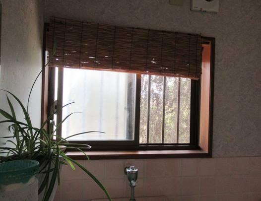 西側の壁をシェードでカバーしたトイレの中の画像